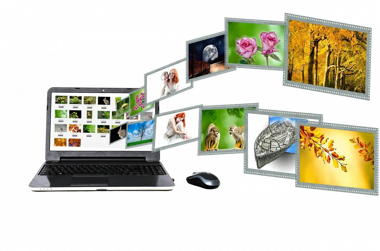 A mouse placed right next to a laptop. The screen of the laptop is full of images while many of them are flying out of the screen.