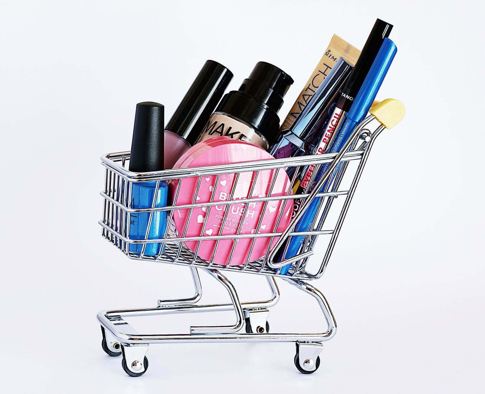 A small-sized metal shopping cart full of big-sized make-up items.