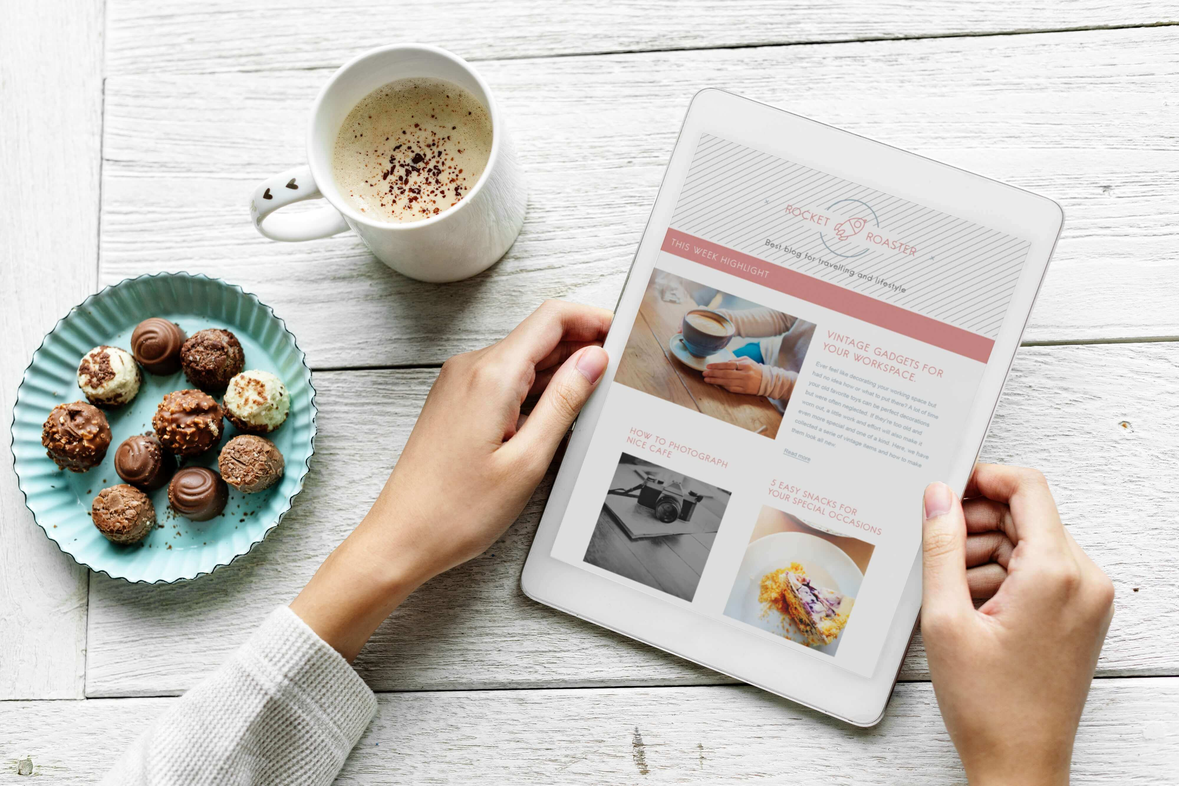 A white table with a cup of coffee and a plate of sweets placed over it. A pair of female hands are carrying a tablet showing some blog posts.
