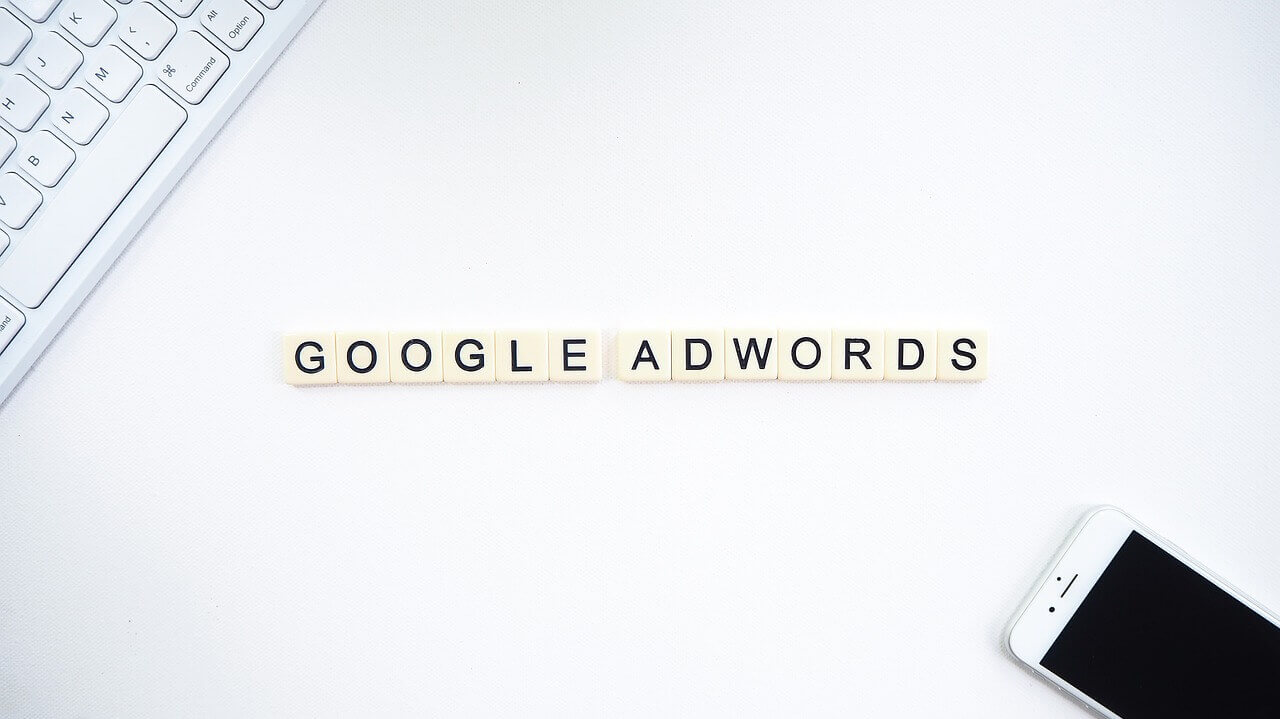 The words *Google AdWords* displayed on a white table. Part of a keyboard is visible on one corner of the table and a cell phone on the other.