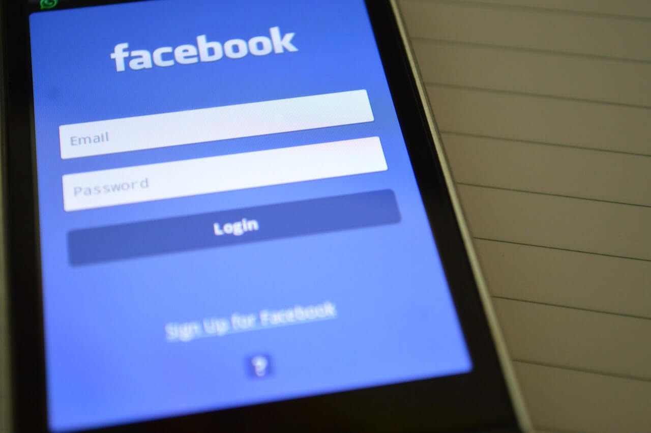 A closeup of a cell phone showing the login page for the Facebook Mobile app.