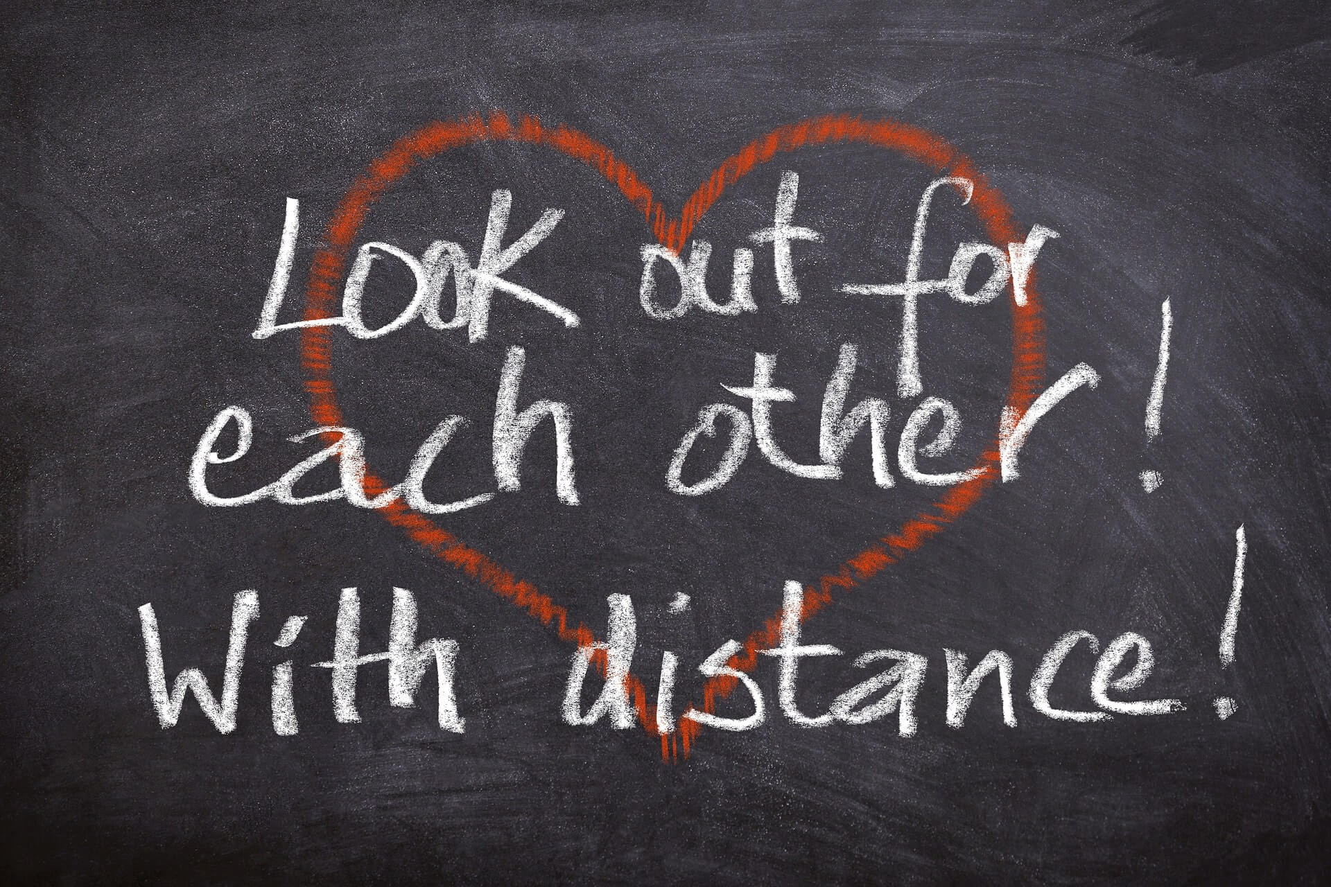"A statement written on the blackboard in white with a red heart says, ""look out for each other from distance"". it refers to helping each other during the current coronavirus outbreak."