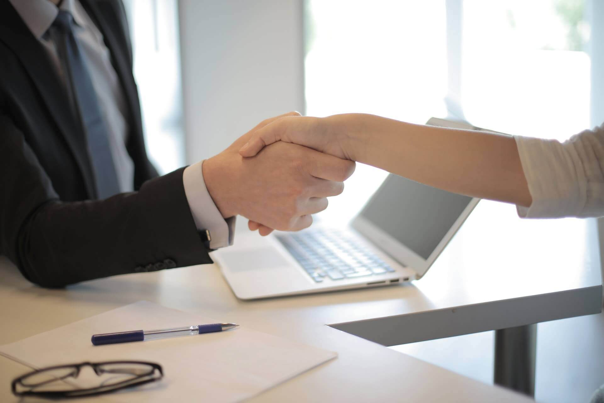 A person in a black suit shaking hands with a lady in white with an office background, referring to staying employed during the current crisis of the corona pandemic.