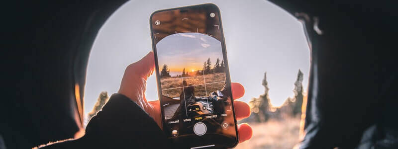 A person taking a picture with his cellphone. The image itself reflects the power of pictures, so it holds an important position in the SEO process for bloggers