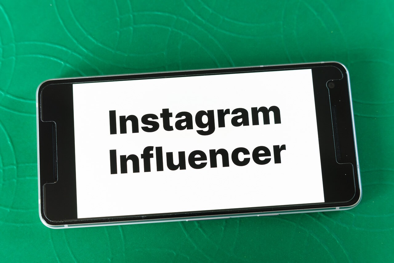 A mobile screen on a green background saying *instagram influencer* in black and on a white screen.